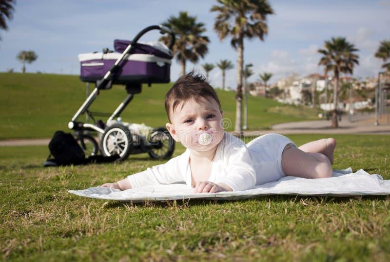 Charmant babymeisje die op een groen gras liggen stock afbeelding