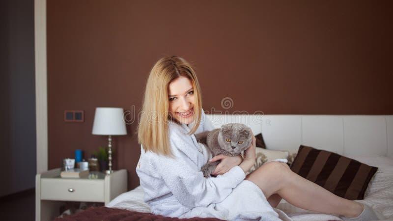 Charmant blondemeisje in een Badstof witte robe in haar flatspelen met een kat stock foto