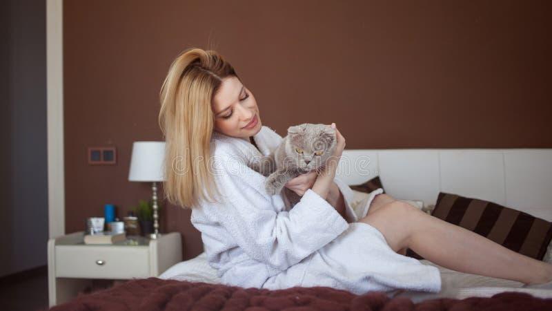 Charmant blondemeisje in een Badstof witte robe in haar flatspelen met een kat stock afbeelding