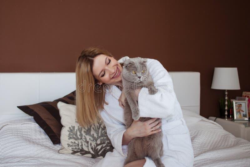 Charmant blondemeisje in een Badstof witte robe in haar flatspelen met een kat stock foto's