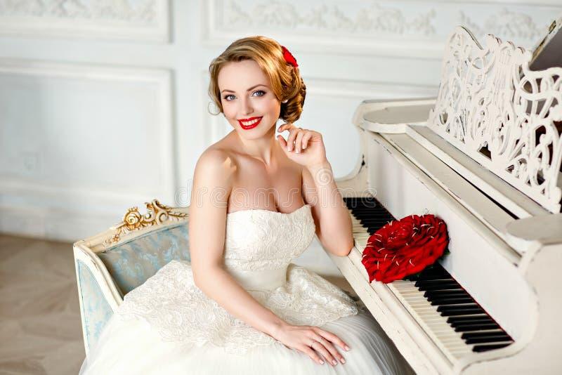 Charmant blondemeisje met mooie glimlach in een witte kantkleding stock afbeelding