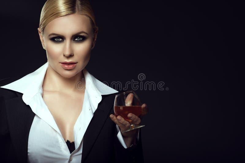 Charmant het glimlachen blond dragend wit mannelijk overhemd en het houden van een glas brandewijn royalty-vrije stock afbeeldingen