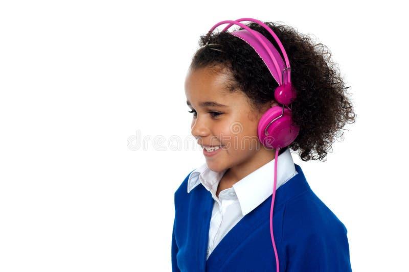 Charmant jong jong geitje die aan muziek luisteren stock foto