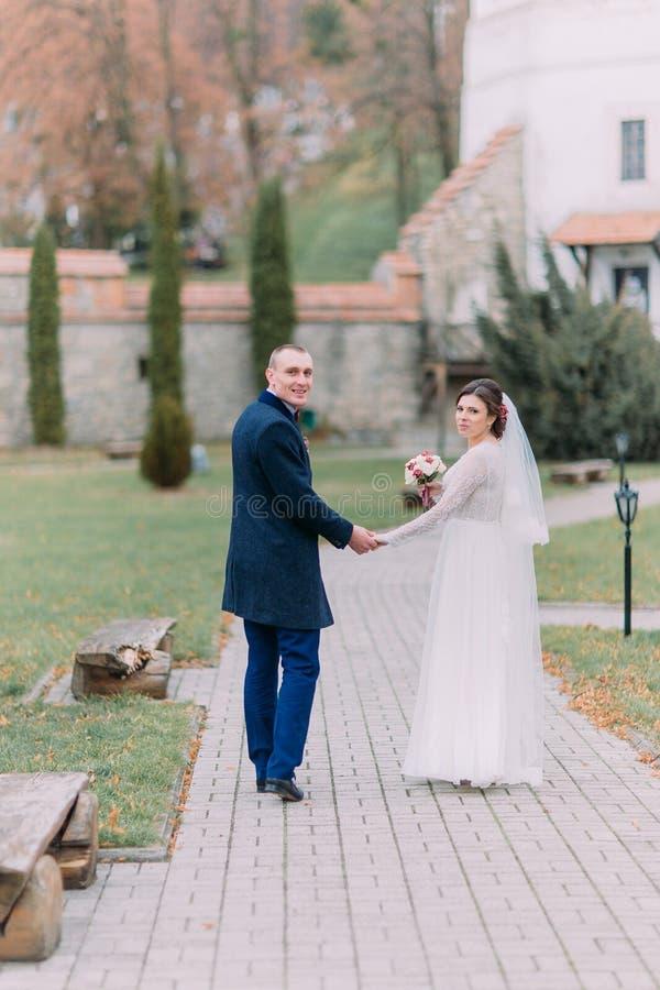 Charmant jonggehuwdepaar die bij huwelijksdag in openlucht op mooi groen park lopen royalty-vrije stock afbeeldingen