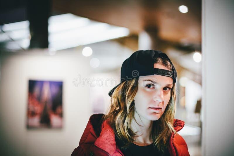 In charmant meisje in rood jasje die modieus GLB dragen stock foto