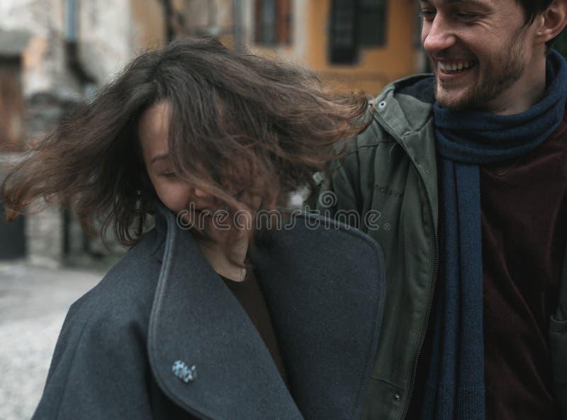 Charmant paar in een kleding die onderaan de straat lopen stock fotografie
