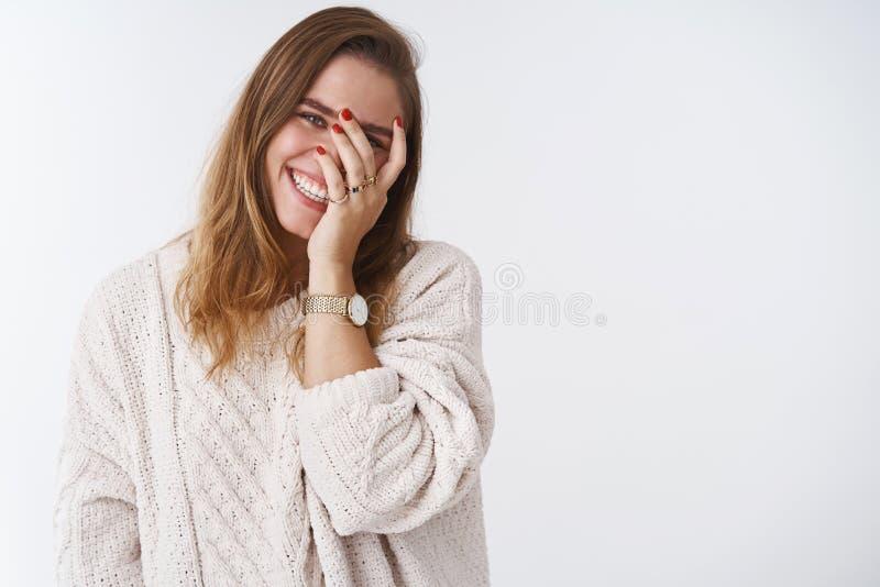 Charmant positief leuk flirty teder Kaukasisch volwassen meisje overhellend hoofd dat het dwaze gluren facepalming door vingers stock afbeelding