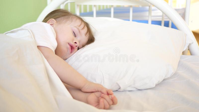 Charmante babydalingen in slaap op wit bed in zijn bed in ruimte thuis concept slaapkind het kind wil slapen en royalty-vrije stock foto's