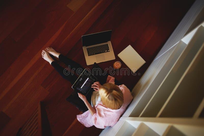 Charmante bedrijfsvrouw die van huis werken terwijl het hebben van ontbijt stock foto