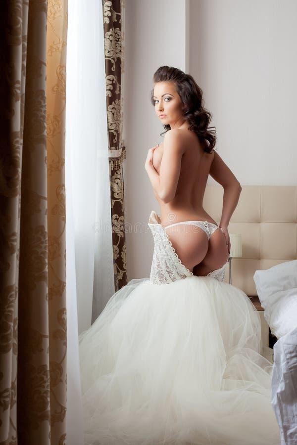 Charmante bruid die bij camera in hotelruimte ontkleden royalty-vrije stock afbeelding