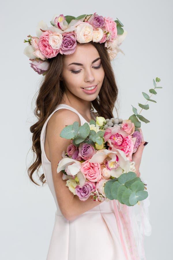 Charmante bruid die in kroon van rozen bloemboeket bekijken stock afbeeldingen