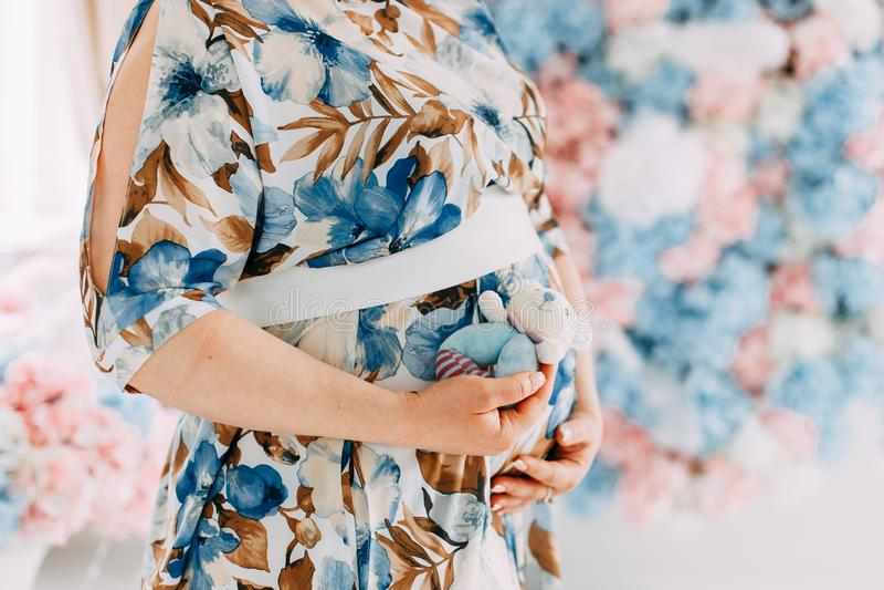 Charmante buik die de zwangere vrouw in kleding omhelst royalty-vrije stock afbeeldingen