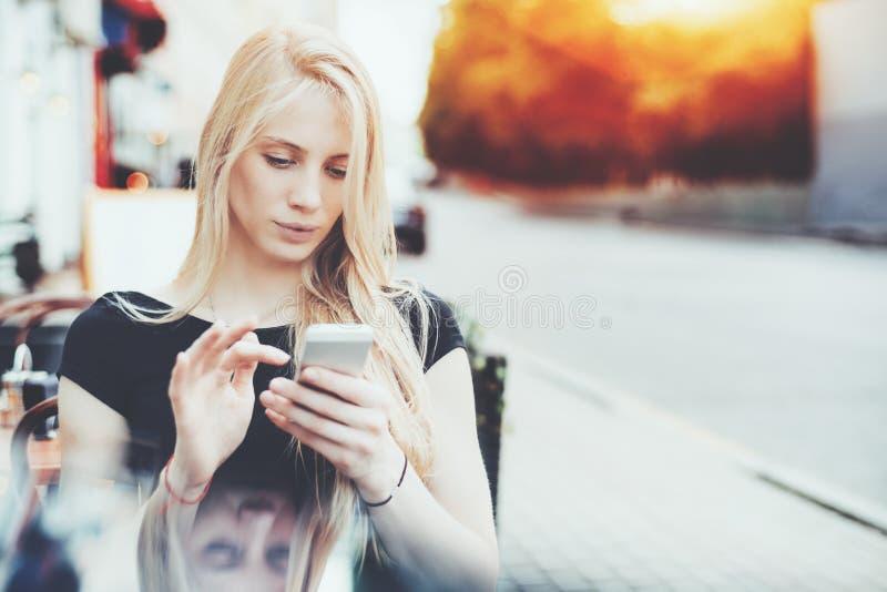 Charmante dame met slimme telefoon in straatbar stock afbeelding