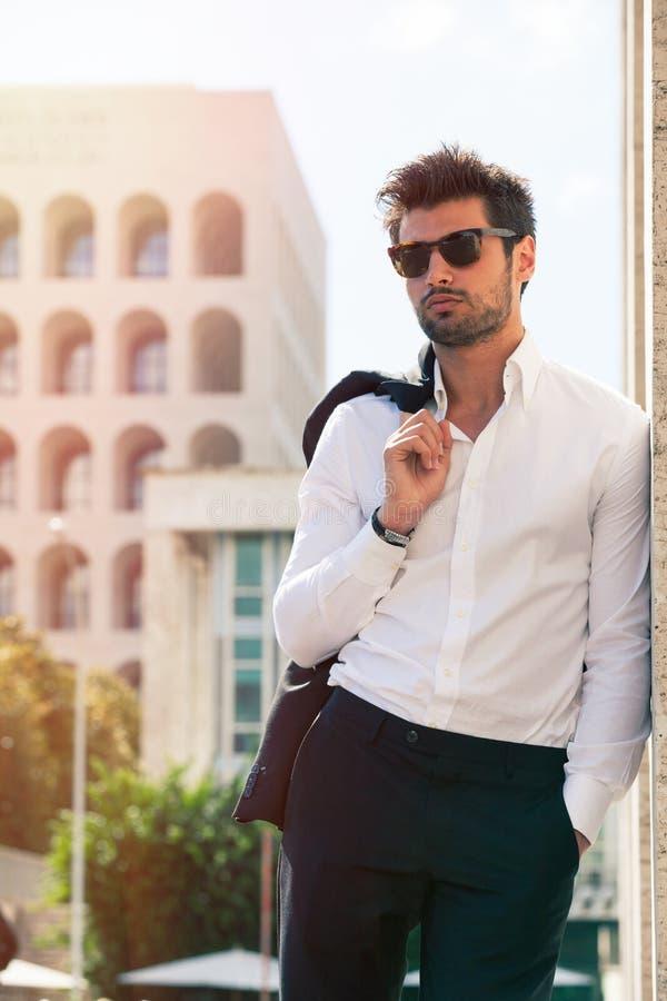 Charmante en modieuze jonge mens met zonnebril stock afbeelding