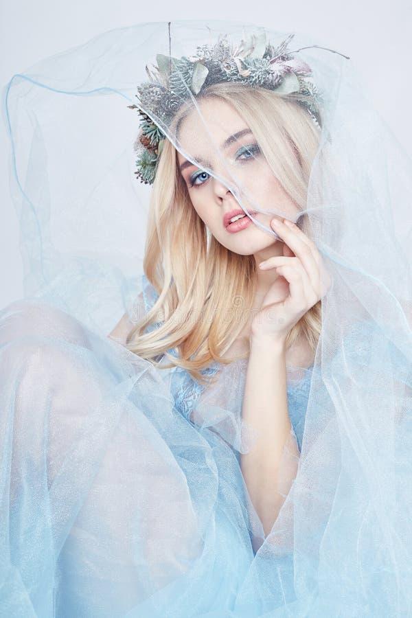 Charmante feevrouw in een blauwe etherische kleding en een kroon op haar hoofd op witte achtergrond, zacht geheimzinnig blondemei stock afbeeldingen