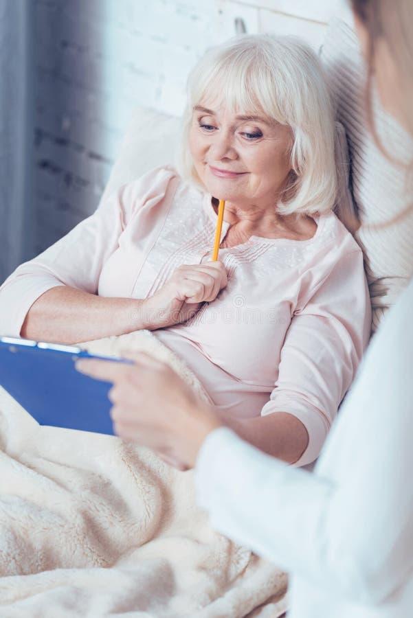 Charmante gepensioneerde die de verzekering in het ziekenhuis ondertekenen stock foto's