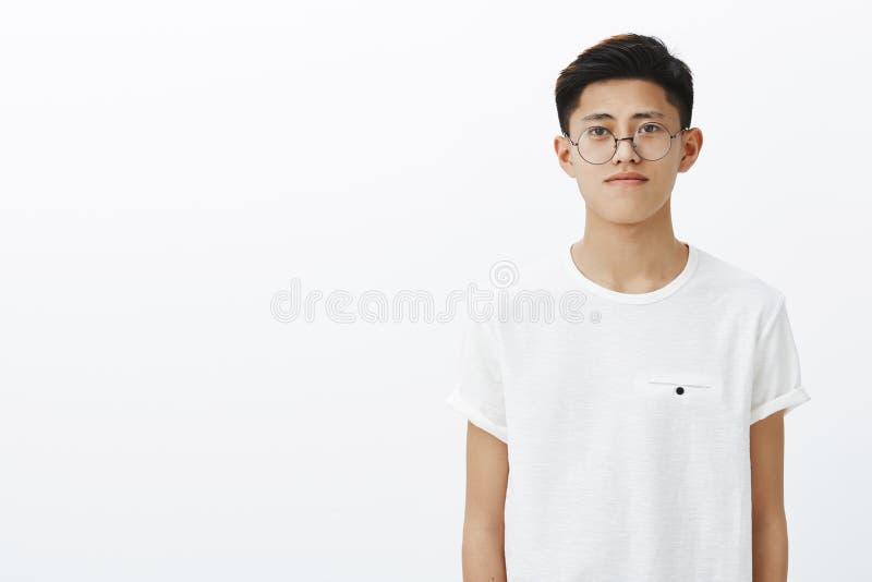 Charmante jonge Chinese kerel in in glazen en t-shirt die zich aan rechterkant van exemplaarruimte bevinden met vriendschappelijk royalty-vrije stock afbeeldingen