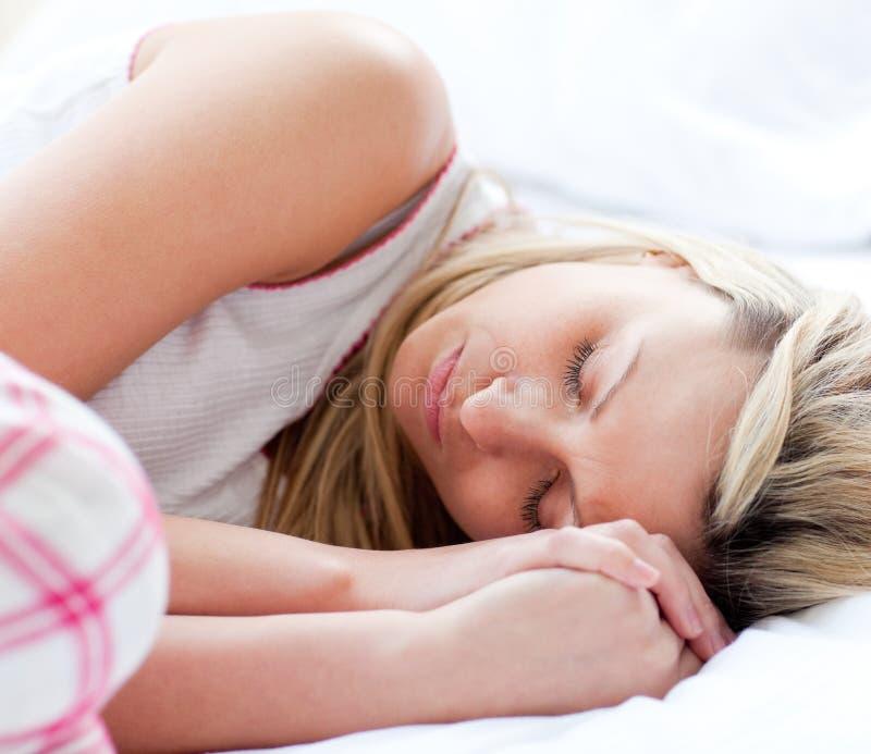 Charmante jonge vrouwenslaap op een bed stock fotografie