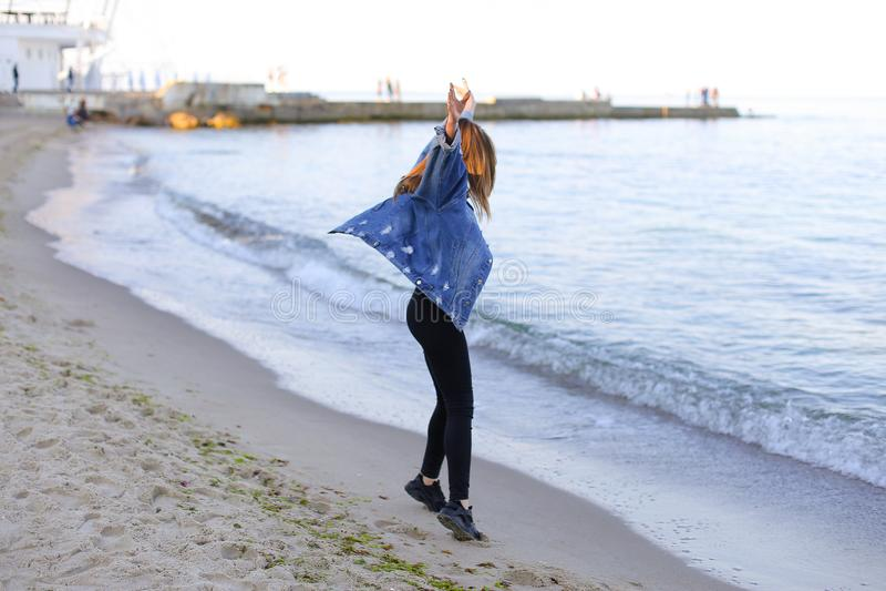 Charmante meisjesgangen langs kust en merrily dwazen rond op zand royalty-vrije stock foto's