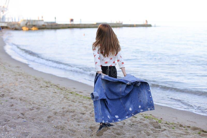 Charmante meisjesgangen langs kust en merrily dwazen rond op zand royalty-vrije stock afbeelding