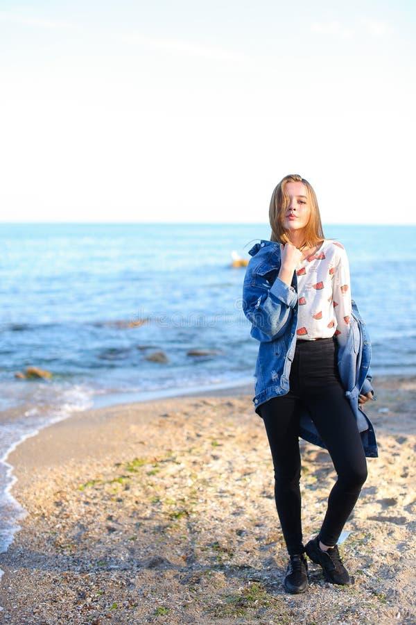 Charmante meisjesgangen langs kust en merrily dwazen rond op zand royalty-vrije stock fotografie