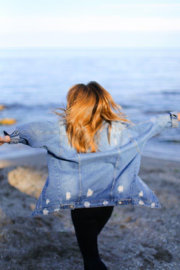 Charmante meisjesgangen langs kust en merrily dwazen rond op zand royalty-vrije stock afbeeldingen