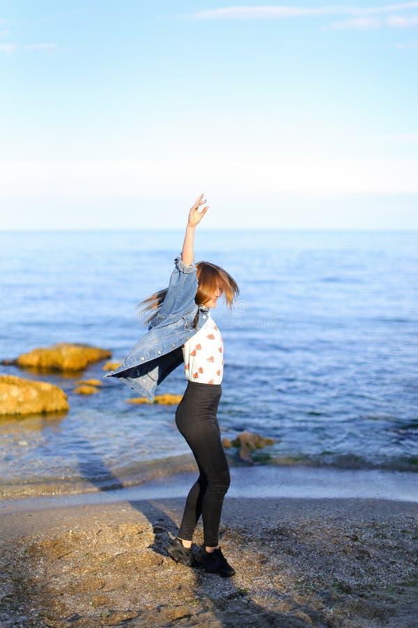 Charmante meisjesgangen langs kust en merrily dwazen rond op zand stock foto