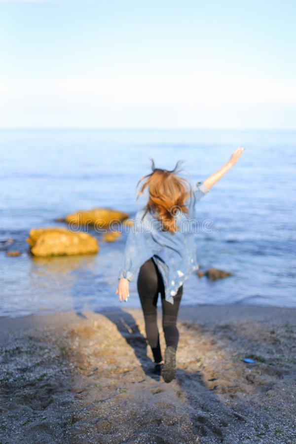 Charmante meisjesgangen langs kust en merrily dwazen rond op zand stock afbeeldingen