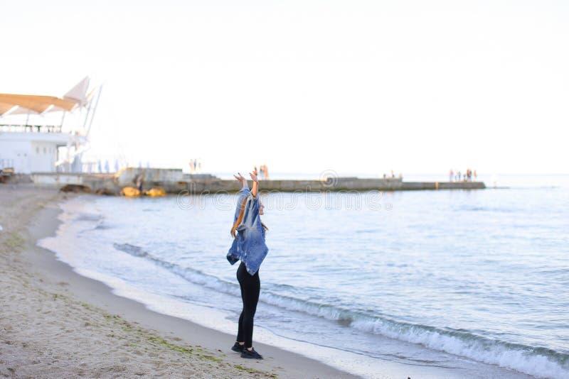 Charmante meisjesgangen langs kust en merrily dwazen rond op zand royalty-vrije stock foto