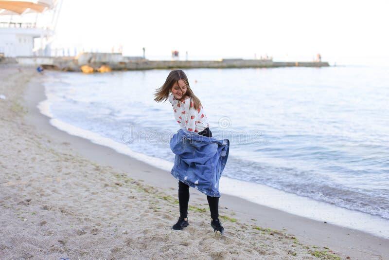 Charmante meisjesgangen langs kust en merrily dwazen rond op zand stock afbeelding