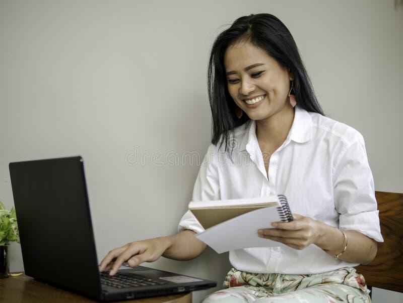 Charmante mooie freelancer die in koffiewinkel een boek in hand houdt, typend op laptop toetsenbord met het glimlachen gezicht stock afbeelding