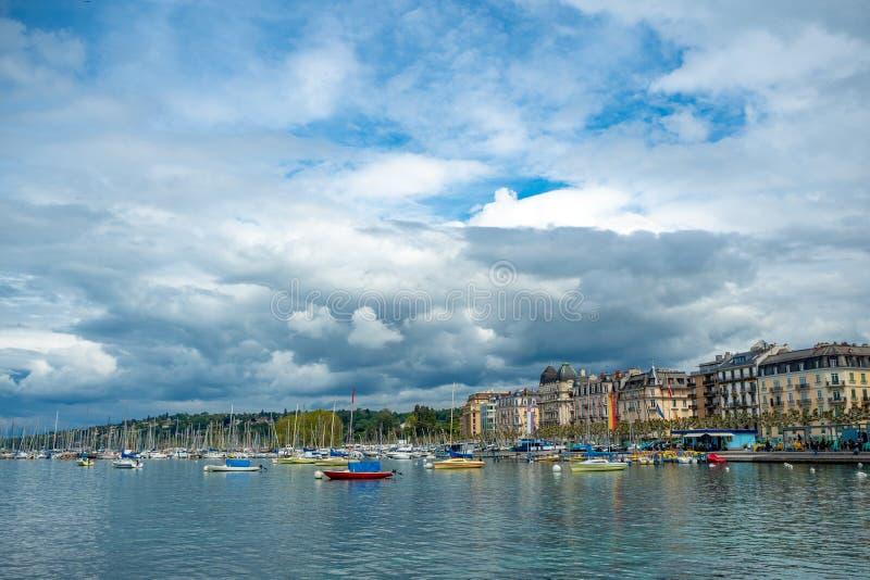 Charmante panoramamening van boten die in het meergebouwen van Genève drijven op achtergrond van de wolken de blauwe hemel royalty-vrije stock foto's