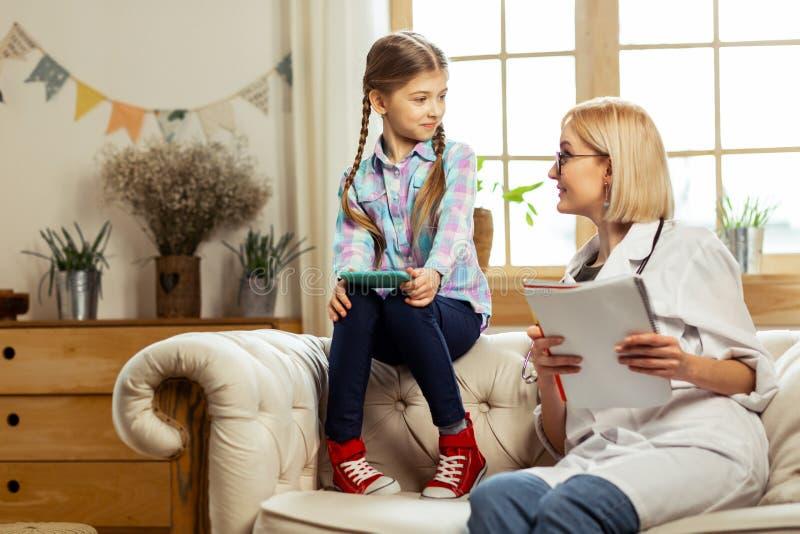 Charmante pediater die nota's maken tijdens een gesprek met ziek kind stock fotografie