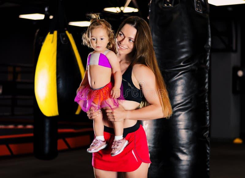 Charmante sportvrouw met haar dochter het stellen tijdens opleiding stock afbeeldingen