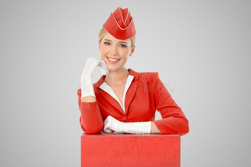 Charmante Stewardess Eenvormig Dressed In Red en Koffer stock fotografie