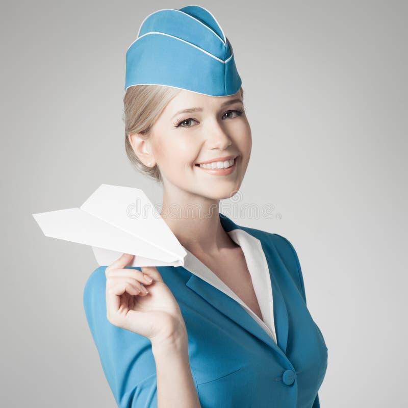 Charmante Stewardess Holding Paper Plane ter beschikking. Gray Background stock foto