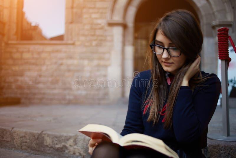 Charmante tienerzitting in openlucht met open boek royalty-vrije stock afbeeldingen