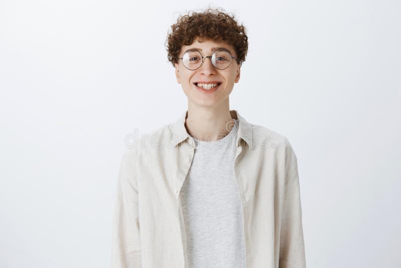 Charmante vriendschappelijk-kijkt hipster kerel in ronde glazen en overhemd met het krullende kapsel hoofd overhellen en leuk gli royalty-vrije stock fotografie
