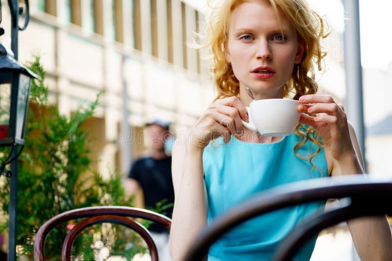 Charmante vrouw die coffe bij stoepkoffie drinken stock fotografie