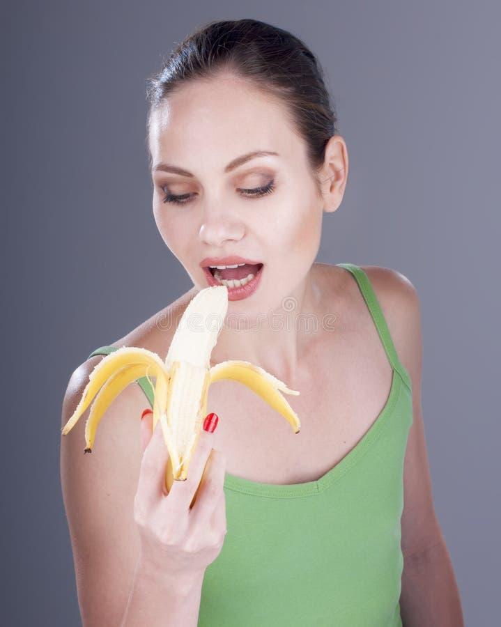 Charmante vrouw die een banaan eten royalty-vrije stock foto