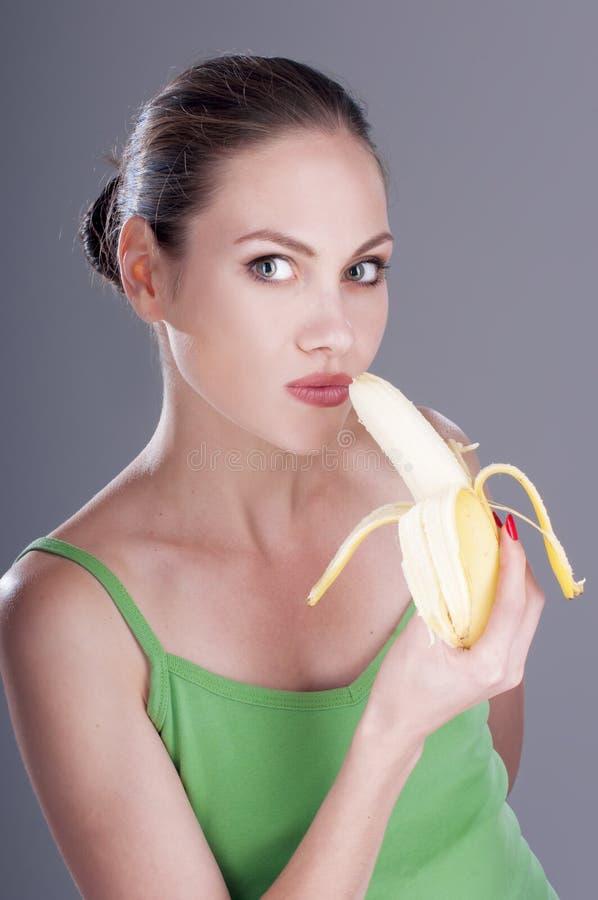 Charmante vrouw die een banaan eten royalty-vrije stock afbeeldingen