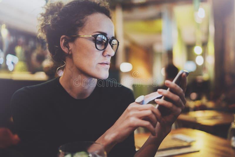 Charmante vrouw die glazen dragen die e-mailbericht op mobiele telefoon lezen tijdens rust in koffiewinkel Bokeh en gloedeffect royalty-vrije stock fotografie