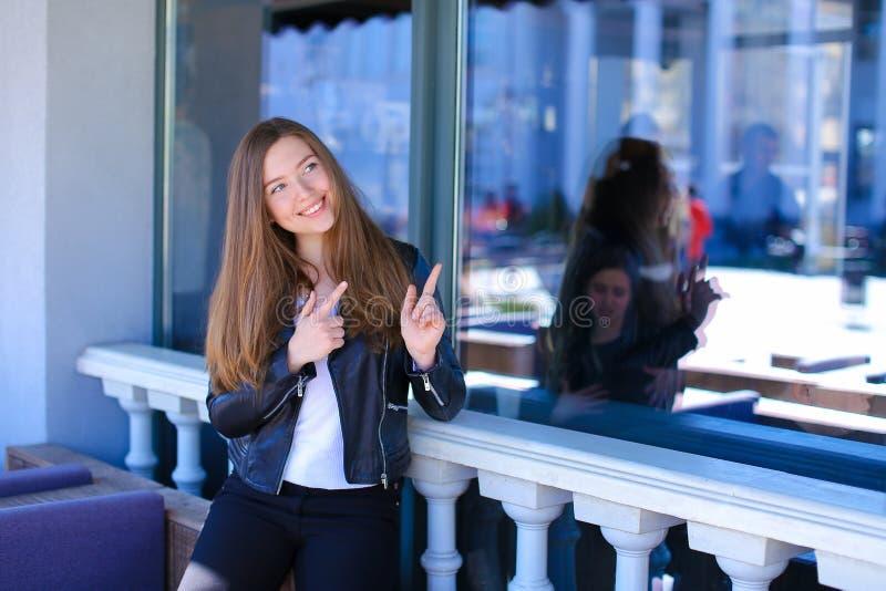 Charmante vrouw die zich dichtbij venster van straatkoffie bevinden met wijsvingers royalty-vrije stock foto
