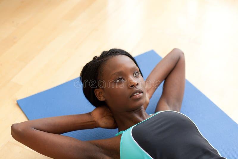 Charmante vrouw in gymnastiekkleren die zitten-UPS doen royalty-vrije stock afbeelding