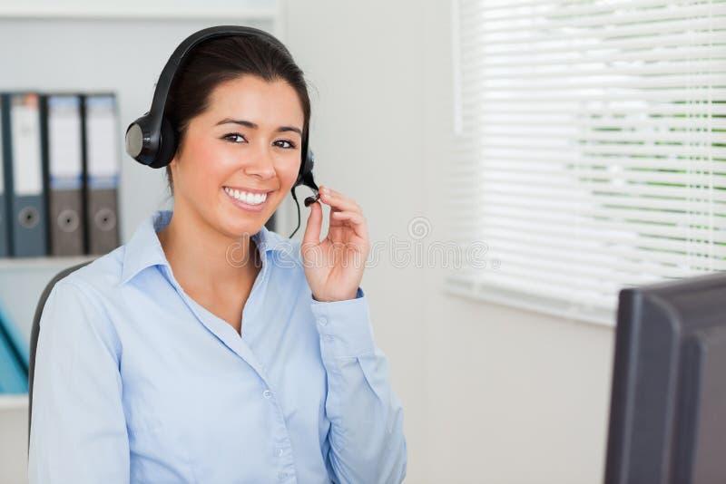 Charmante vrouw met een hoofdtelefoon die klanten helpt stock foto's