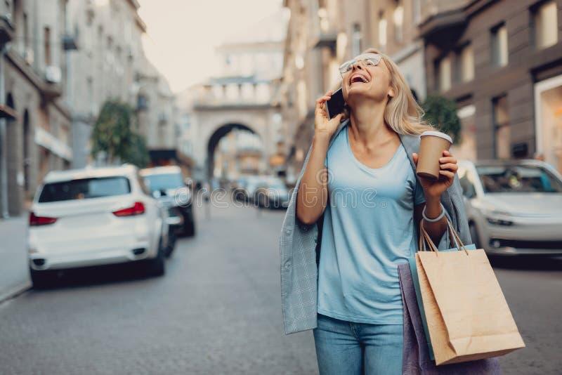 Charmante vrouw met hete drank die bij cellphone en het lachen spreken royalty-vrije stock foto