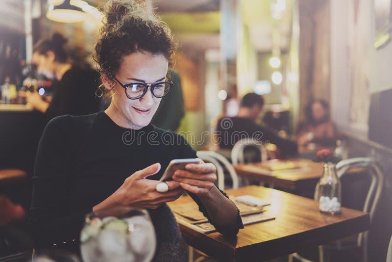 Charmante vrouw met mooi de tekstbericht van de glimlachlezing op mobiele telefoon tijdens rust in koffiewinkel Bokeh en gloed stock fotografie