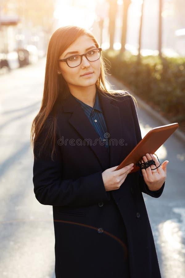 Charmante vrouwelijke student status in openlucht met haar digitale tabletpc stock fotografie