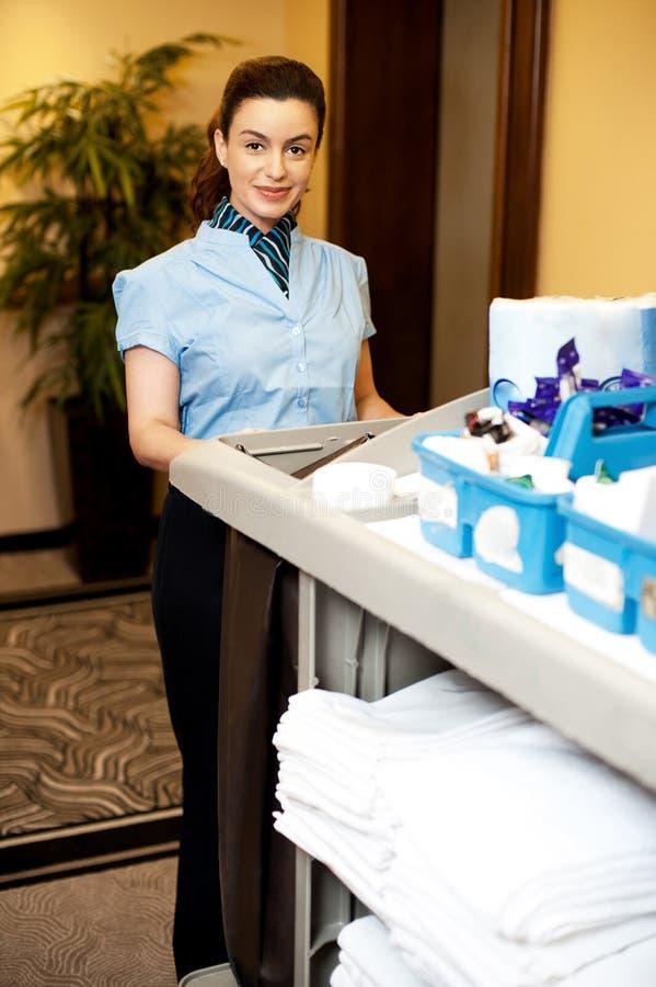 Charmante vrouwelijke uitvoerende holdingstoiletries kar stock afbeelding