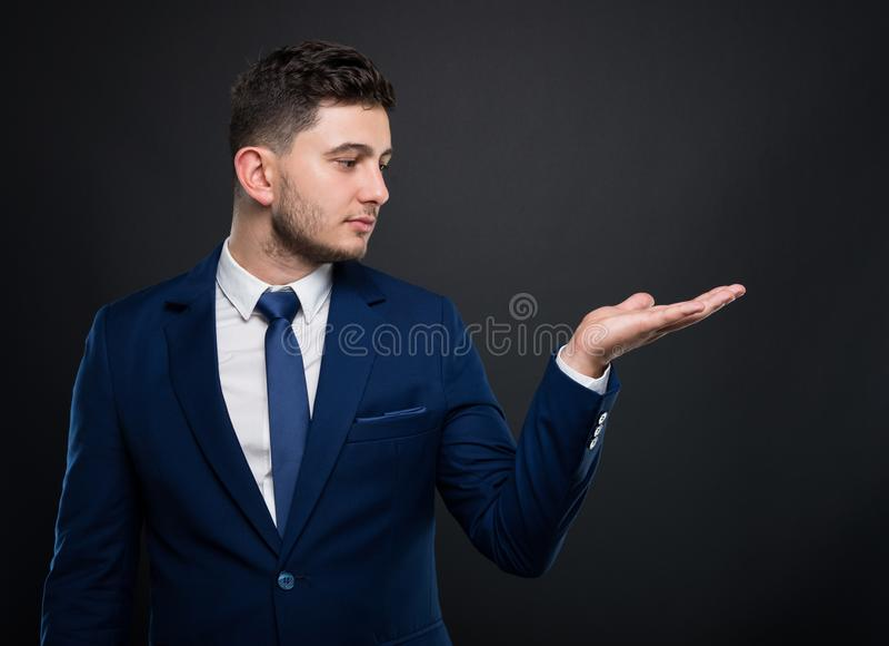 Charmante zakenman die zijn palm standhouden royalty-vrije stock foto's